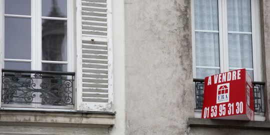 Un panneau à vendre sur un immeuble situé à Paris à proximité de la Tour Eiffel