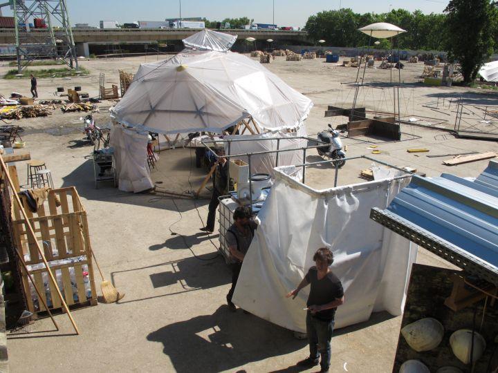 Même si les préparatifs ont déjà commencé, difficile d'imaginer que, sur ces grandes friches industrielles, va être élaborée une ville éphémère, bâtie à partir de déchets issus pour la plupart des 60000 m2 des hangars du Printemps.